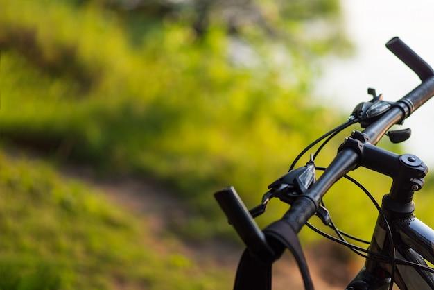 Primer plano de bicicleta de montaña en el bosque al atardecer con copyspace
