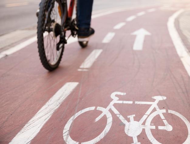 Primer plano de la bicicleta que monta la bicicleta en la carretera con signo de carril bici