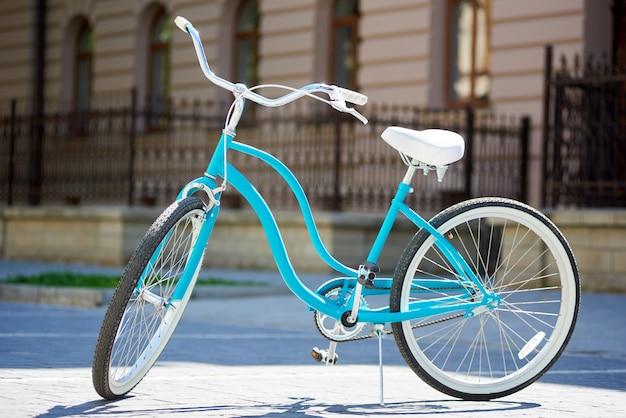 Primer plano de una bicicleta retro azul en la luz del sol de un día de verano