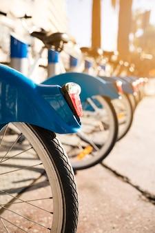 Primer plano de bicicletas de pie en una fila en un estacionamiento en alquiler