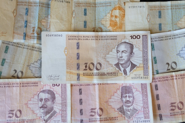 Primer plano de los billetes de bosnia y herzegovina repartidos en la superficie de la moneda