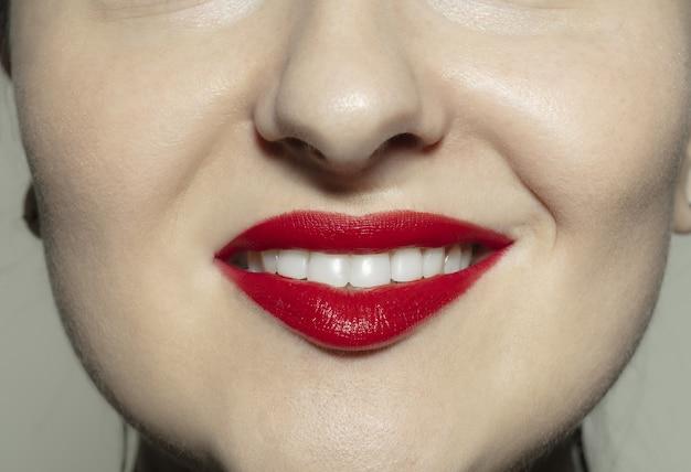 Primer plano boca femenina con labios de brillo rojo brillante