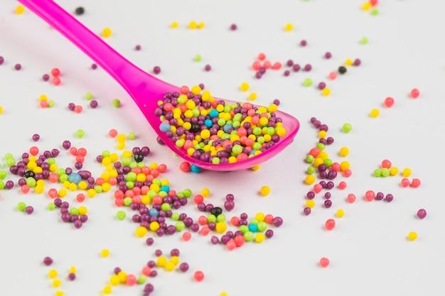 Primer plano de bolas de azúcar dulce color multi en cuchara de plástico