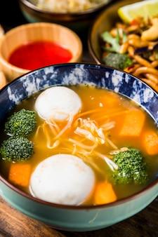 Primer plano de bolas de pescado y sopa de verduras