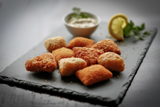Primer plano de bolas de queso de patata frita o croquetas sobre placa de piedra oscura