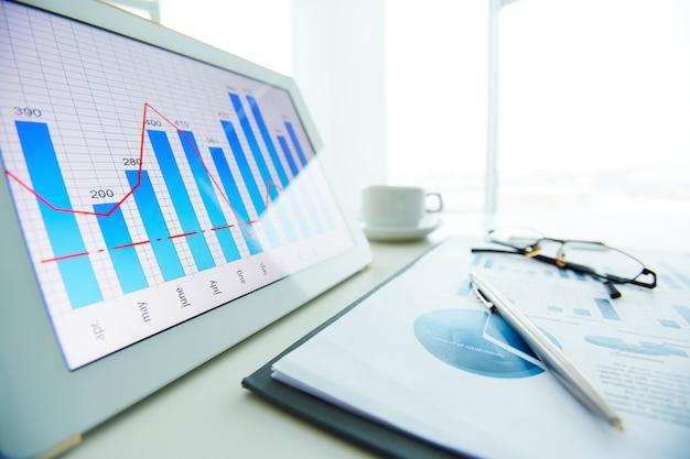 Primer plano de bolígrafo sobre informe económico con la ventana de fondo