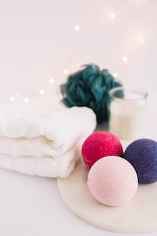 Primer plano de bombas de baño de colores en tablero blanco cerca de servilletas y loofah