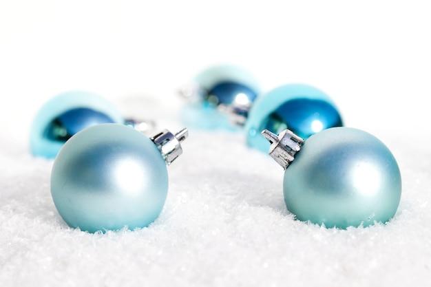 Primer plano de bombillas de navidad azul en la nieve.