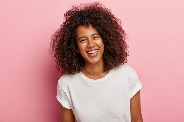 Primer plano de una bonita adolescente con piel oscura, cabello afro rizado, sonríe, tiene dientes blancos, se ríe sinceramente de una buena broma, se divierte con un amigo cercano, usa camiseta blanca todos los días