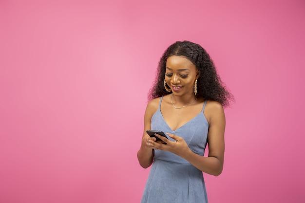 Primer plano de una bonita chica afroamericana en un estado de ánimo emocionante sosteniendo su teléfono
