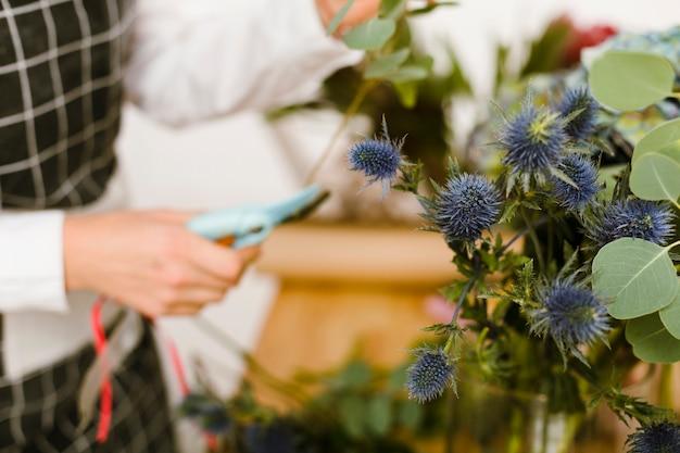 Primer plano borrosa floristería cortando flores para ramo
