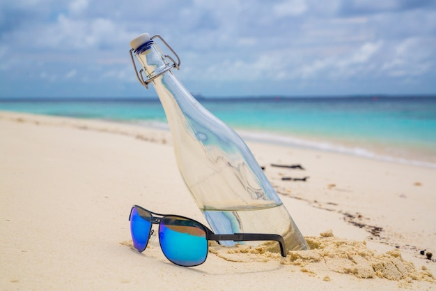 Primer plano de una botella de agua y gafas de sol en la playa de arena junto al mar