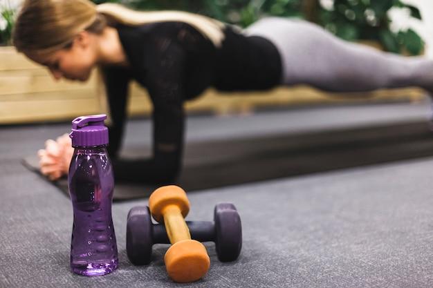 Primer plano de la botella de agua y pesas frente a mujer haciendo flexiones