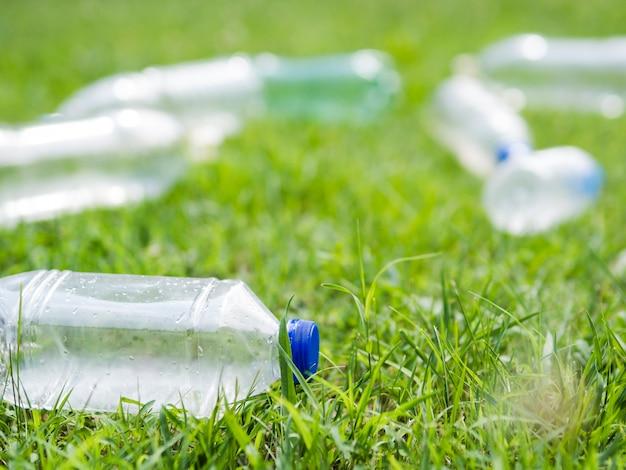 Primer plano de la botella de agua plástica de desecho en el césped en el parque