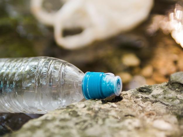 Primer plano de la botella de agua de residuos de plástico en el exterior