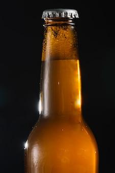 Primer plano de una botella de cerveza sobre fondo negro