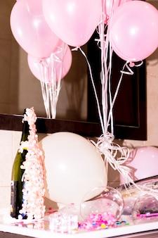 Primer plano de la botella de champán con confeti y globos de color rosa en el escritorio