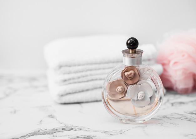 Primer plano de la botella de perfume frente a la toalla y la esponja en la superficie de mármol