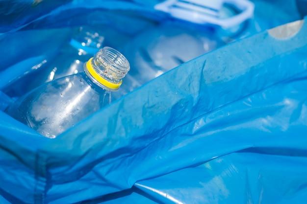 Primer plano de la botella de plástico de residuos en la bolsa de basura azul