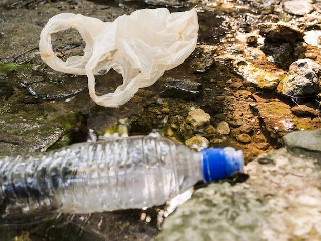 Primer plano de la botella de plástico de residuos en charco