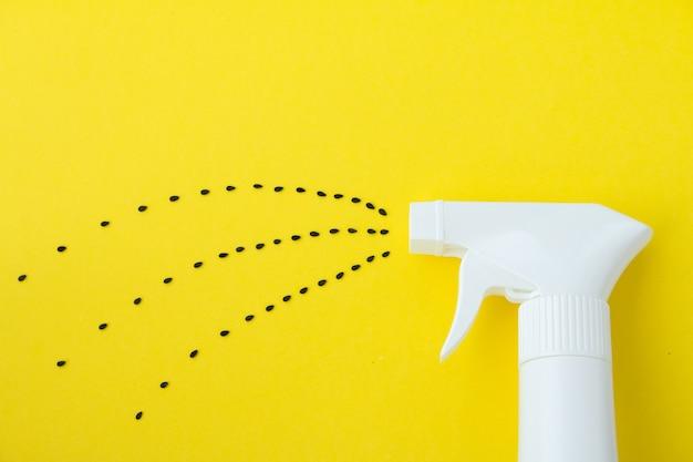 Primer plano de la botella de spray blanco sobre fondo amarillo con la línea de pulverización de semillas negras de saseme, agua pulverizada o concepto de siembra