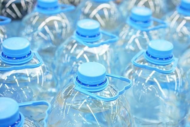 Primer plano de botellas de agua potable de plástico de cinco litros, enfoque suave