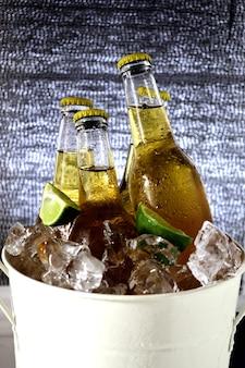 Primer plano de botellas de cerveza con hielo y rodajas de limón en un balde
