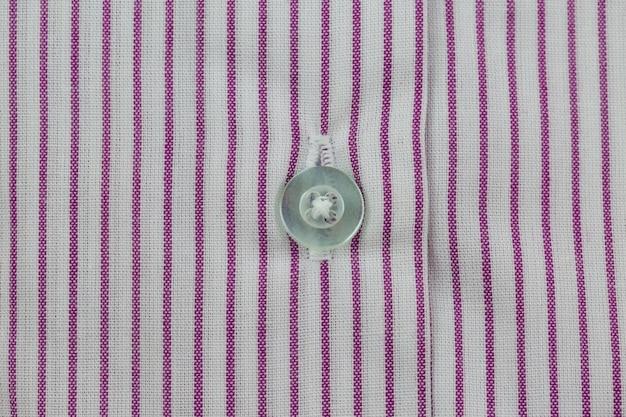 Primer plano del botón blanco en el patrón de camisa roja y blanca a rayas