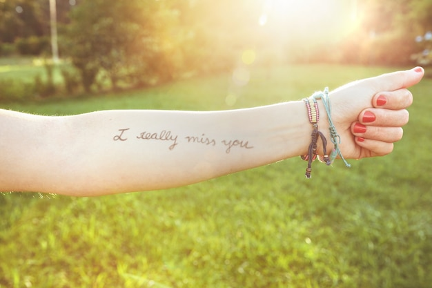 Primer plano del brazo femenino con el texto `` realmente te extraño '' escrito en la piel sobre un fondo de naturaleza soleada