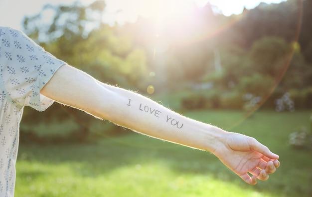 Primer plano del brazo masculino con el texto -te amo- escrito en la piel sobre un fondo de naturaleza soleada