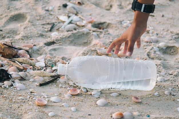 Primer plano de brazos los niños están recogiendo botellas de plástico que se dejan en la playa.