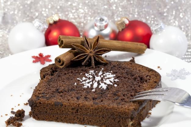 Primer plano de un brownie con canela y adornos de árbol de navidad rojo en el fondo