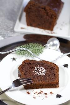 Primer plano de un brownie en una placa blanca junto a la decoración de plata de navidad