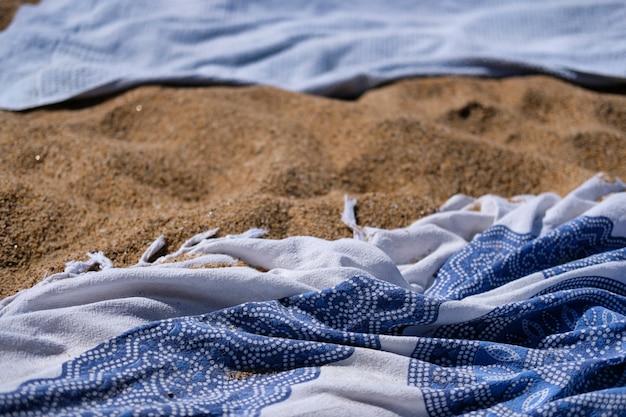 Primer plano de una bufanda decorativa sobre fondo de arena