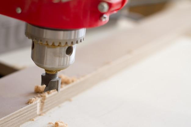 Primer plano de la cabeza de la perforadora con boquilla en el taller de muebles