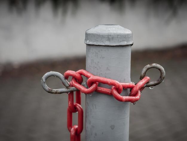 Primer plano de una cadena roja alrededor de un poste