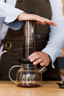 Primer plano de café aeropress: prensa de barista al dispositivo y gotas de café se vierte a través de aeropress a la olla