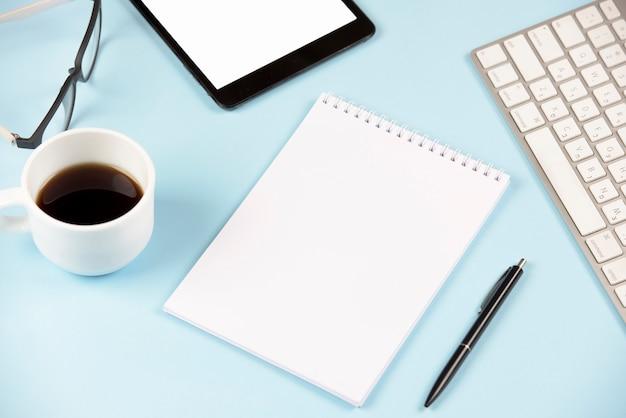 Primer plano de café; los anteojos; tableta digital; teclado; bloc de notas de espiral en blanco y pluma contra fondo azul