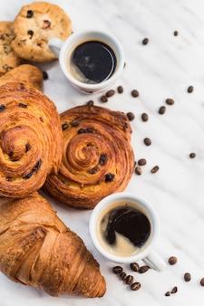 Primer plano de café y croissant con grano de café sobre mármol
