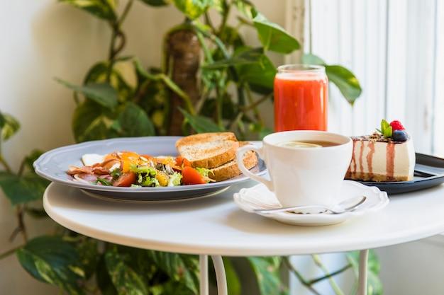 Primer plano de café; desayuno; tarta de queso y batido rojo en mesa blanca