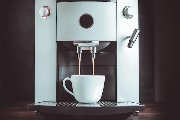 Primer plano de café espresso que vierte de la máquina
