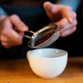 Primer plano de café tamizado en taza por hombre