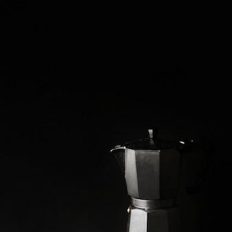 Primer plano de la cafetera en el fondo negro
