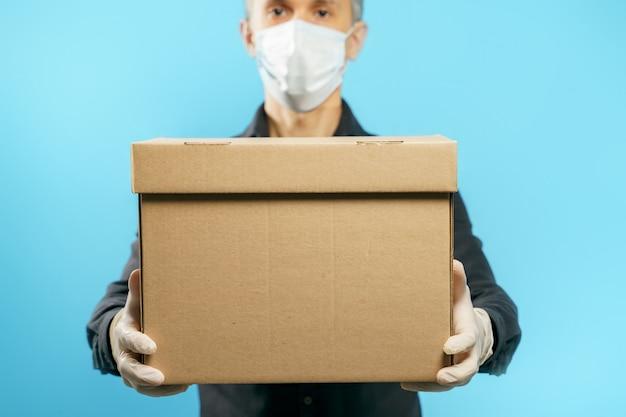 Primer plano de una caja de cartón en manos de un joven en una máscara de protección médica y guantes en azul. entrega segura
