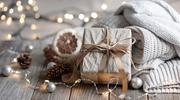 Primer plano de una caja de regalo, detalles de una decoración navideña festiva y elementos tejidos sobre un fondo borroso con bokeh.