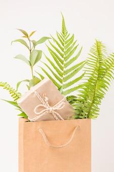 Primer plano de una caja de regalo y hojas de helecho verde en bolsa de papel marrón