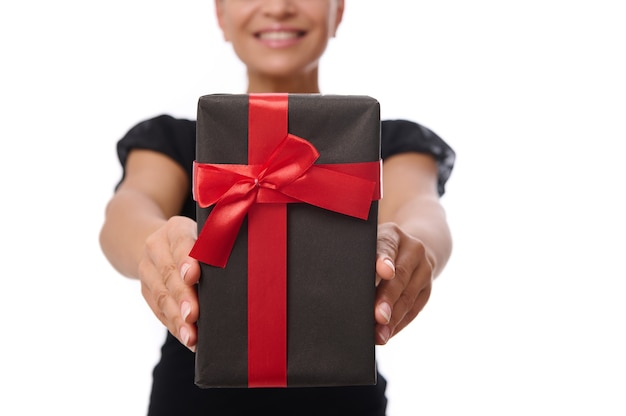Primer plano de una caja de regalo negra con cinta roja en manos de una mujer sonriente vestida de negro aislado sobre fondo blanco con espacio de copia. concepto de aniversario, viernes negro y celebración.