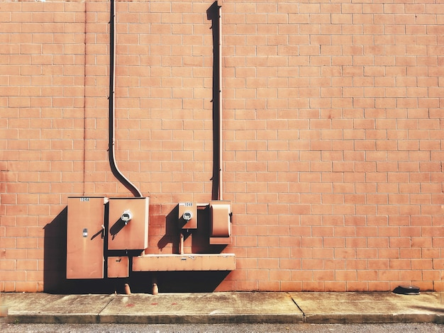 Primer plano de cajas de fusibles eléctricos en una pared de ladrillo marrón