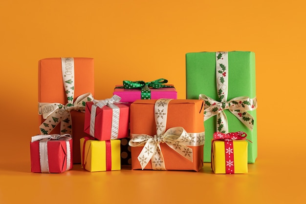 Primer plano de cajas de regalo multicolores en el fondo naranja, humor navideño