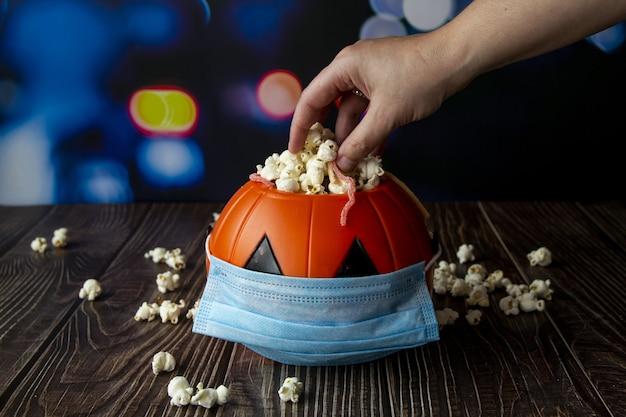 Primer plano de una calabaza de halloween con palomitas de maíz y una máscara sanitaria-concepto de la nueva normalidad